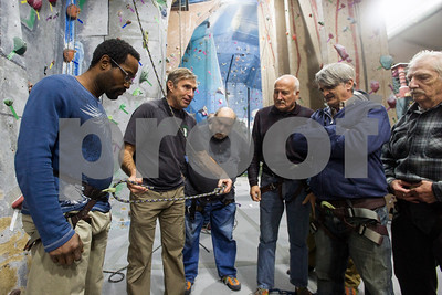 Robert Layman / Staff Photo  Ray Hamilton, left, watches as Steve Lulek, right, teaches the group to tie a figure eight follow through knot before they belay Friday night at the Green Mountain Rock Climbing Center, Nov. 10 2017.