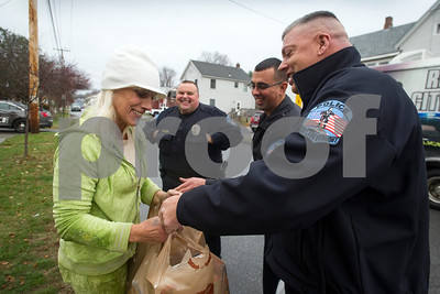 Robert Layman / Staff Photo Gina Morrill, left, smiles as she recieves a bag of food from Rutland City Police Chief, Brian Kilcullen, and Officer Emilio Rosario, second from left, outside her home on Library Avenue in Rutland Monday afternoon. The food was collected by Jackie Lorman, who is the wife of Sgt. Keith Lorman, center. Sgt. Lorman said the house was once a scene of frequent law enforcement encounters but has changed for the better.
