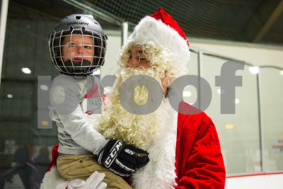 Robert Layman / Staff Photo Santa, aka, TJ Moran, who might just be the worlds best procrastinator, took time out of his busy holiday schedule to skate around with children who showed up in large numbers at the the Giorgetti Arena Thursday, Dec. 21, 2017. Seen here he holds a young Brody Kendall, 3, to hear about some last minute Christmas gifts.