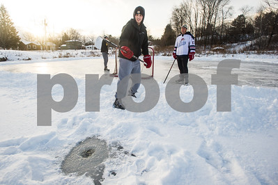Robert Layman / Staff Photo Ryan Bellomo picks his hockey stick out of a hole in Combonation Pond after checking the ice depth before playing a pick up game Wednesday afternoon, Dec. 27, 2017. Bellomo said the ice's depth went below the tip of his hockey stick and pick up games will be happening despite the frigid temperatures.