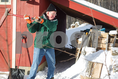 Robert Layman / Staff Photo State Representative James Harrison (R) chops wood outside his home in North Chittenden Dec. 27, 2017.