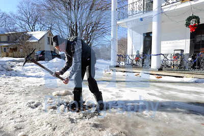 Jeb Wallace-Brodeur / Staff Photo Lewis Neill uses a pick ax Wednesday to clear the ice from a storm drain outside his home in Montpelier. Warm weather is creating puddles of snow melt throughout the region with rain expected today.