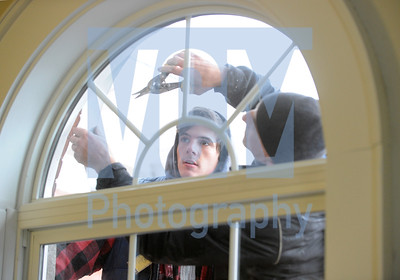 Jeb Wallace-Brodeur / Staff Photo Todd Carrier, right, and his son Luke, working for Randall Contracting, install trim around new energy efficient windows Thursday at Capstone Community Action's Brook Street School building in Barre.