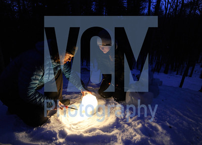 Jeb Wallace-Brodeur / Staff Photo Onion River Sports employees Tristan Von Duntz and Brooke Isabelle light lanterns Friday night to mark a snowshoe trail in Montpelier's Hubbard Park. The shop hosted their 20th annual Snowshoe Romp in the park with a fire, hot cocoa and snowhoes demos for the public.