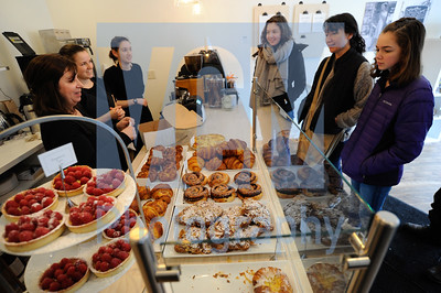 Jeb Wallace-Brodeur / Staff Photo Customers line up to buy fresh pastries at the Bohemian Bakery on Barre St., in Montpelier which opened for business Wednesdsay morning. The popular European-style bakery and cafe recently moved from their previous location in Calais to a newly-renovated spot at the corner of Hubbard St. Working the counter fom left are co-owner Annie Bakst, Astrid O'Connor and Becky Peterson.