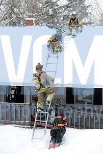 Jeb Wallace-Brodeur / Staff Photo Firefighters from Barre Town and Barre City use ladders Tuesday to access and vent the roof of a burning home on Cutler Corner Road in Barre Town.