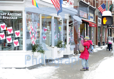 Jeb Wallace-Brodeur / Staff Photo Anne Ferguson of Montpelier takes a photo of hearts on the window of the Coffee Corner in Montpelier Tuesday as the Valentine Phantom once again covered the downtown in paper hearts.