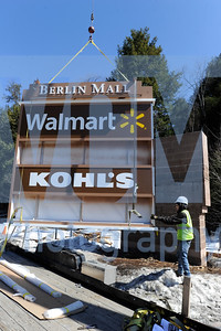 Jeb Wallace-Brodeur / Staff Photo Hatzany Mejias from Poyant Signs of New Bedford, Mass., guides a new sign for the Berlin Mall into place Thursday. The new illuminated sign replaces an older wooden version that was deteriorating.