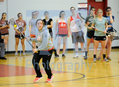 Jeb Wallace-Brodeur / Staff Photo Fifth-year coach Kasey Abbriano, a physical education teacher at Barre City and a former Norwich University player, demonstrates a technique to her girls' lacrosse team during indoor practice at Spaulding High School Thursday. Area teams hope that warmer weather forecasted for next week will allow them to get outside before long.