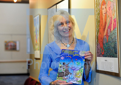Jeb Wallace-Brodeur / Staff Photo Kelley Hunter of Calais poses with her new coloring book and a show of her work at the Barre Opera House on Friday.