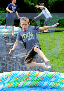 Jeb Wallace-Brodeur / Staff Photo Logan Royer, 8, of Barre Town, gets airborn while playiong a game of slip-n-slide kickball at the Vermont Rustic Moose Summer Camp in Webstrerville Friday.