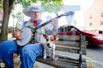 Jeb Wallace-Brodeur / Staff Photo Andrew Webster plays the banjo Wednesday on a bench in downtown Montpelier with his dog Zoey at his side. Webster, who hails from northern Georgia, has been in the area for a few weeks caring for a sick friend and says the people in Vermont are some of the friendliest he's ever encountered.