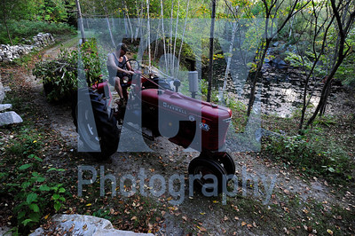 Jeb Wallace-Brodeur / Staff Photo Porter Walbridge, of Barre, drives a tractor carrying brush at the Lodge at Millstone Lodge in Websterville Thursday while helping prepare the property for this Saturday night's FallFire which will feature live music, thousands of candles, a lantern launch and pyrotechnics in a quarry setting.