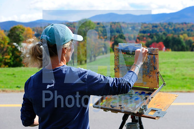 Jeb Wallace-Brodeur / Staff Photo Artist Peg Runcie of Westwood, Mass., paints a foliage scene in Stowe Thursday. Autumnal colors are finally starting to show in some areas.