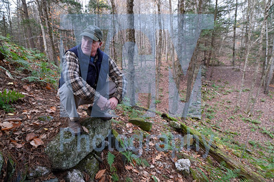 Jeb Wallace-Brodeur / Staff Photo Montpelier Parks Director Geoff Beyer squats on an old stone wall that marks the boundary of Hubbard Park. The parks department is interested in purchasing a couple parcels to add additional acreage.