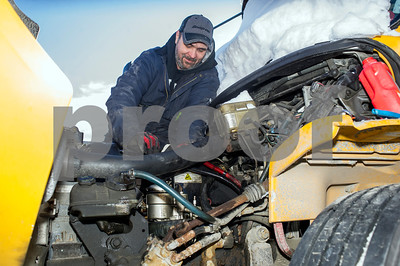 Robert Layman / Staff Photo  Despite the rough week of temperatures and the gelling up of diesel engines,  Eric Gero, Bet-Cha Transit Mechanic, smiles as he cleans out a school bus' fuel filter which has gelled diesel fuel and frozen water in it outside Rutland Town School January 4, 2017.