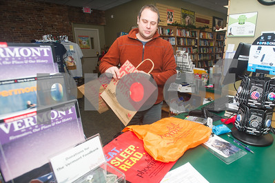 Robert Layman / Staff Photo William Notte, Phoenix Bookstore Manager, shows off some of his business' alterantives to single use plastic bags. Notte, whose worked for Phoenix Bookstore since they've opened two years ago, said he's seen a noticeable decrease in the amount of customers asking for bags, which he cites as a reason for the change. Notte said one concern from customers has been carrying books in the rain, but said his reuseable options, one of woven material and another a collapseable style are both waterproof.