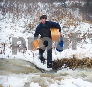 Robert Layman / Staff Photo  O' Leary crosses moving water while holding the bird boxes.