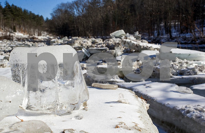 Robert Layman / Staff Photo A large block of ice several inches thick sits on top other pieces of similar size lined up along the Ottauquechee River in Bridgewater.