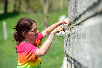 Jeb Wallace-Brodeur / Staff Photo Hannah Peatman, of Montpelier, working for A.D. Building of East Montpelier, repoints cement in an 1887 granite mausoleum turned tool shed Friday at the Cutler Cemetery in East Montpelier.
