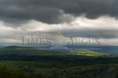 Sunlight peaks through the clearing rain clouds in Plainfield on Sunday.  Josh Kuckens/Staff Photo