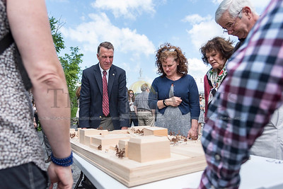 Governor Phil Scott surveys a scaled architectural model of the Taylor Street Transit Center at a groundbreaking ceremony on Tuesday in Montpelier.  Josh Kuckens/Staff Photo