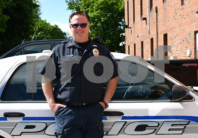 Rutland City Police School Resource Officer Chris Green, posing in front of his cruiser behind the station in Rutland Wednesday morning. (Robert Layman / Staff Photo)