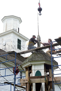 Jeb Wallace-Brodeur / Staff Photo Jason Norris, left, of Glover, and Adam King, of Peacham, working with noted historic preservationist Jan Lewandowski, prepare to remove a spire from the top of a steeple segment after it was lowered Tuesday from the Old West Church in Calais. The 1823 church is getting a major overhaul this sumer and organizers hope to replace the steeple sometime in the autumn.