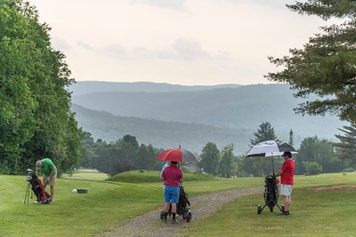 A foursome tees off before approaching storms at Blush Hill in Waterbury on Monday.  Josh Kuckens/Staff Photo