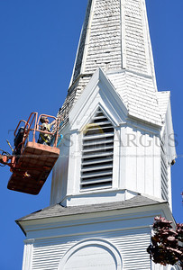 Jeb Wallace-Brodeur / Staff Photo Bill Lacillade, of East Barre, replaces some damaged shingles Thursday on the steeple of the Union Congregational Church in Roxbury. Lacillade is volunteering his time to help paint the historic church.