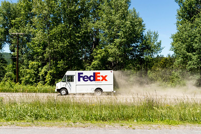 A FedEx delivery vehicle kicks up dust on the Paine Turnpike alongside Berlin Pond on Tuesday.  Josh Kuckens/Staff Photo