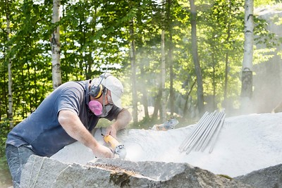 Sculptor Chris Miller begins grinding on a new sculpture along the Millstone Trails in Websterville on Tuesday.  Josh Kuckens/Staff Photo