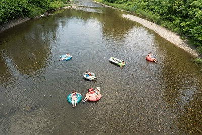 Tubers seeking relief from the heat wave float down the Mad River along Main Street in Waitsfield on Sunday.  Josh Kuckens/Staff Photo
