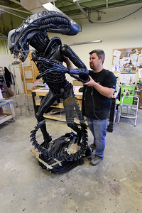 Jeb Wallace-Brodeur / Staff Photo Artisit Mike Turner attaches an arm Wednesday to a huge sculpture of the movie creature Alien at his Barre studio. Turner has been working on the intricately detailed fiberglass and resin piece for more than a year. It will be displayed at Comicon in New York City later this year.