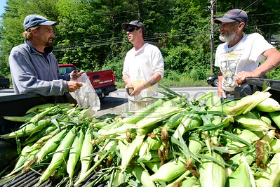 Jeb Wallace-Brodeur / Staff Photo Dave Darling, left, and Steven Larocque, right, from Liv Silly Farm in Barnet, sell fresh corn on the cob Thursday to Damien Dunham of Cabot. The farm sells corn and other veggies at the intersection of Routes 2 and 302 in Montpelier on weekdays from 8-3.