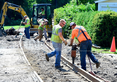 Jeb Wallace-Brodeur / Staff Photo Ryan Loucy, left, and Steve Miller, from Vermont Rail Systems, drive spikes Thursday on a repaired stretch of track in Barre. A minor derailment Wednesday damaged the tracks at Ayers Street. The street should reopen to traffic after repaving is completed Friday.