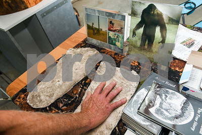 Brian Gosselin holds up his hand to a plaster cast of a bigfoot print he found in the woods. (Robert Layman / Staff Photo)