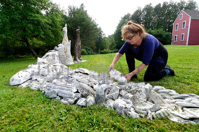 Artist Leslie Fry, of Winooski, arranges plaster pieces Wednesday for a large-scale installation on the lawn of the Kent Museum in Calais. The bronze and plaster work will be part of the annual Art at the Kent show. This year's show, entitled Backstory, runs from Sept. 7 to Oct. 7 with an opening celebration on Sept. 8. (Jeb Wallace-Brodeur / Staff Photo)