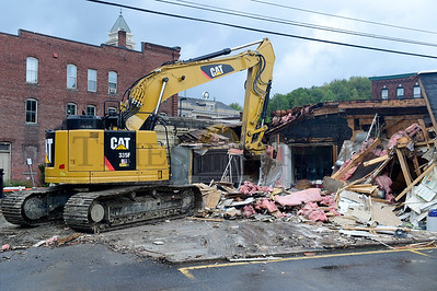 A heavy equipment operator from DuBois Construction demolishes the Montpelier Beverage and Redemption Center on Main Street Thursday morning. The building is being removed to make way for a bike path. (Jeb Wallace-Brodeur / Staff Photo)