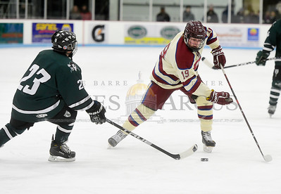 Spaulding sophomore Owen Kresco tries to carry the puck past the defense of Stowe junior Andrew McDermott during the first period of their game Wednesday.