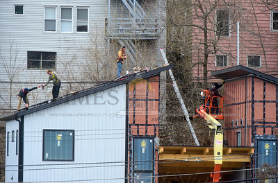 Workers install solar panels Wednesday on the room of a new residential unit being constructed on River St., in Montpelier.