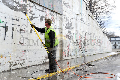 Bill Demell, from the Barre street department, washes loose paint off a retaining wall Wednesday on Summer St., in Barre in preparation for the installation of a new mural in a few weeks.