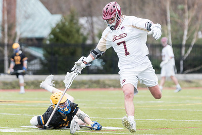 Norwich midfielder William Conroy, right, loses his stick after a check from Emmanuel College defender Connor Dooley, right, on Saturday as the cadets advance to the GNAC semifinals in Northfield.
