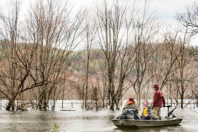Sarah Garceau, left, and James Wallace, center, get settled as Lindley Barrett, right, navigates through unusually high waters at the Wrightsville Reservoir boat launch in Middlesex on Sunday.