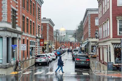 Pedestrian cross a rainy Langdon Street in Montpelier on Saturday.