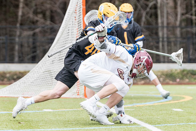 Norwich attacker Parker Campbell, center, gathers his balance amid the defensive efforts of Emmanuel College's Connor Prangley, left, as the Cadets advance to the GNAC semifinals on Saturday in Northfield.