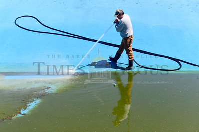 Richard Thompson, with the Montpelier Recreation Department, uses a high-pressure hose to clean the bottom of the municipal pool Wednesday as preparations begin for summer recreation in the city.