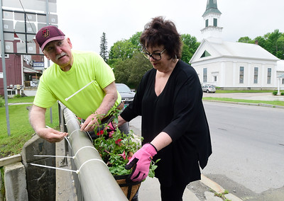Arthur and Annie Kramer, with the Williamstown Beautification Guild, attach flower boxes Thursday to the railing of a bridge in Williamstown. The guild plants and maintains flower arrangements in 13 barrels and 18 bridge planters in town.