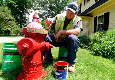 Alex Knudsen, from the Montpelier Water Department, paints fire hydrant Wednesday in Montpelier. The city's numerous hydrants get a fresh coat of paint every few years.