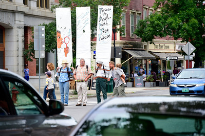 Demonstrators stand in the crosswalk at State and Main Streets in Montpelier on Thursday during a monthly protest against fossil fuel extraction and the banks that support it. From left are: Susanna Lewis, of Bradford, Duncan Nichols, of Thetford, and Douglas Smith, of Sharon.